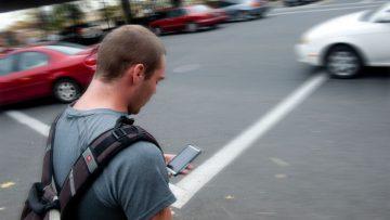 RSE tecnológica: un peatón imprudente cruza una calle si sacar la vista de su celular.