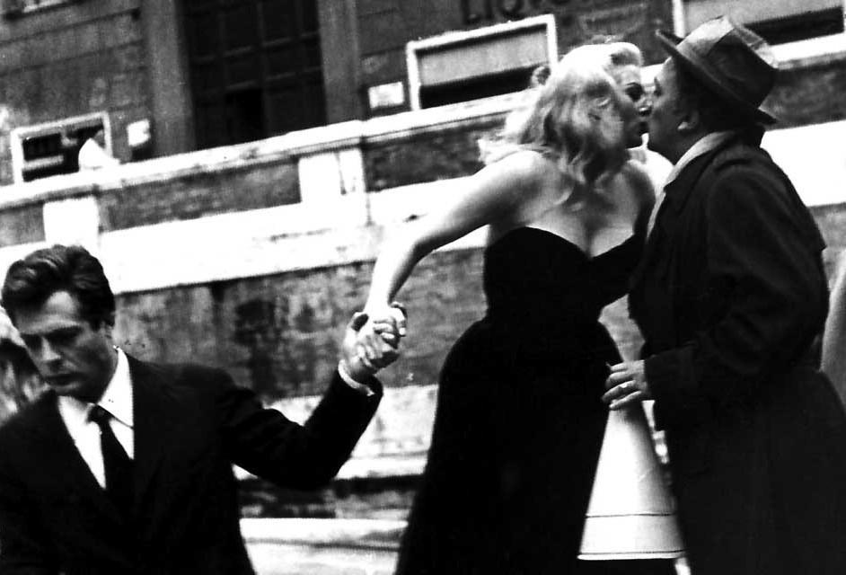 Federico Fellini roba un beso a Anita Ekberg durante un alto en el rodaje.